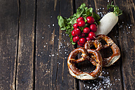 Two pretzels, red radishes, radish and scattered salt grains on dark wood - CSF026989