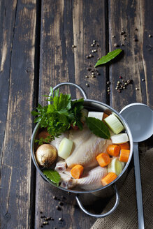 Cooking pot with raw corn-fed chicken, onion, herbs and greens - CSF026995