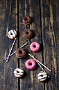 Drinking straws and doughnuts with different icings on dark wood - CSF027007