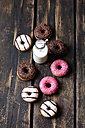 Glass bottle of milk and doughnuts with different icings on dark wood - CSF027010