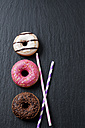 Three doughnuts with different icings and two drinking straws on slate - CSF027013