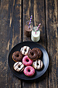 Two glass bottles of milk and cocoa and plate of doughnuts with different icings on dark wood - CSF027016