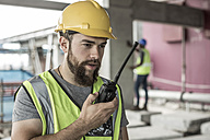Construction worker with walkie-talkie in construction site - ZEF007846