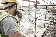 Construction worker with walkie-talkie in construction site - ZEF007858