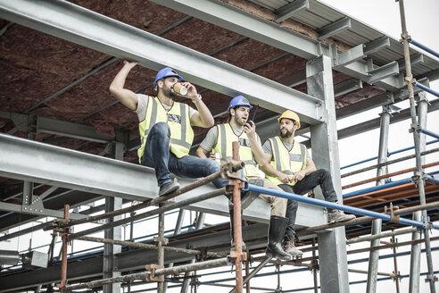 Construction workers having a break on scaffolding - ZEF007882