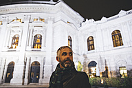 Austria, Vienna, portrait of man in front of Burgtheater by night - AIF000207