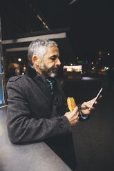 Austria, Vienna, man with Cheese Carniolan sausage and smartphone  by night - AIF000210