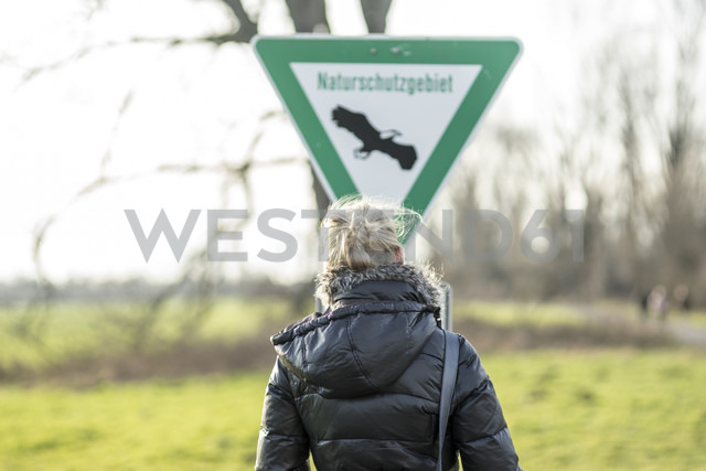 Germany, Neuss, woman in front of nature reserve sign - CHPF000191