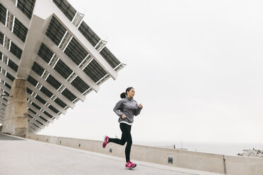 Spain, Barcelona, jogging woman, solar plant in the background - EBSF001206