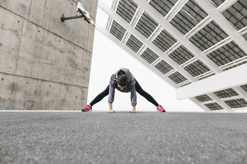 Spain, Barcelona, female jogger, stretching excersice under solar plant - EBSF001212