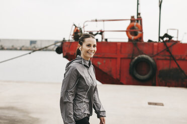 Spain, Barcelona, jogging woman with headphones at harbour - EBSF001218