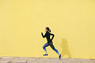 Spain, Barcelona, jogging woman in front of yellow wall - EBSF001221