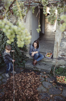 Spain, Asturias, woman sitting at entrance of country house watching her son picking autumn leaves - DAPF000002