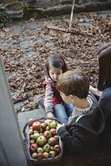 Woman sitting at entrance of country house with her children looking at basket of apples - DAPF000005