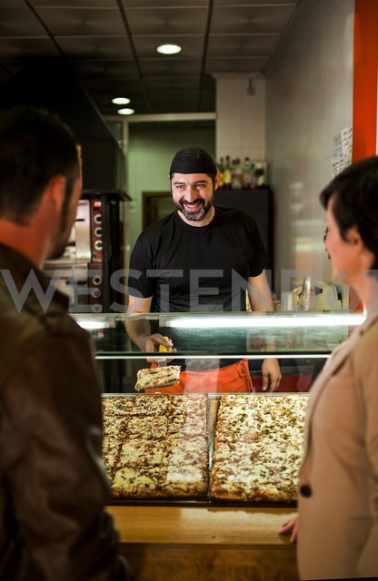 Couple choosing piece of pizza at snack bar - JASF000335