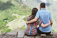 Peru, couple sitting and enjoying the views of Machu Picchu citadel - GEMF000622