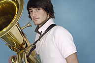Portrait of teenage boy with tuba in front of blue background - GUFF000181