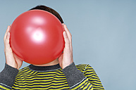 Teenage boy hiding face behind red balloon in front of blue background - GUFF000184