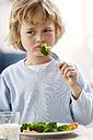 Portrait of unhappy blond boy eating broccoli - GUFF000202