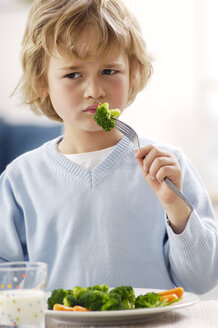 Portrait of unhappy blond boy eating broccoli - GUFF000202
