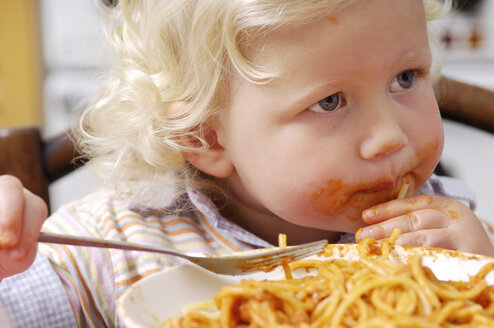 Portrait of little blond girl eating spaghetti with tomato sauce - GUFF000205