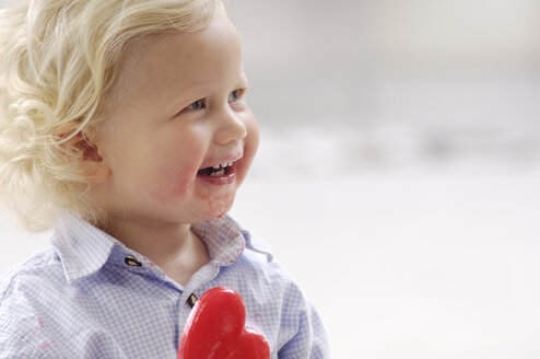 Portrait of smiling little blond girl with heart-shaped lollipop - GUFF000208