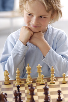 Portrait of smiling little boy playing chess - GUFF000211