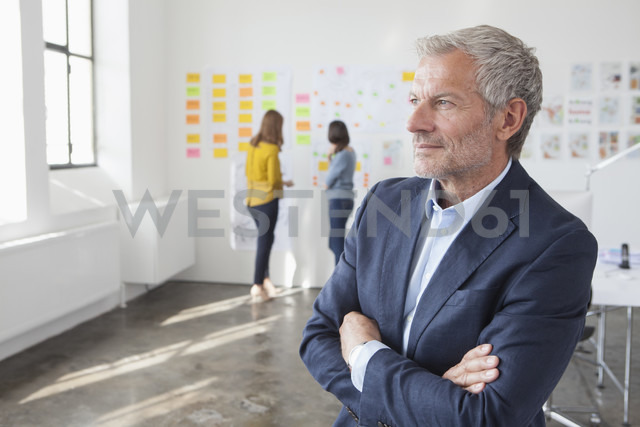 Confident businessman in office thinking - RBF003990