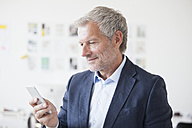 Businessman in office looking at cell phone - RBF003999