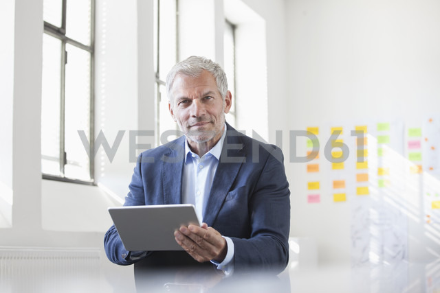 Portrait of businessman in office holding digital tablet - RBF004002