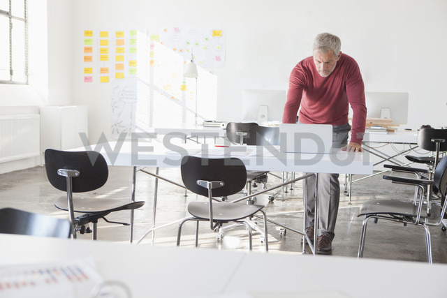 Businessman using laptop in office - RBF004011