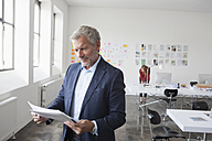 Businessman in office looking at paper - RBF004017