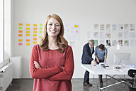 Portrait of smiling young woman in office - RBF004020