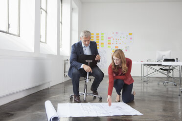 Businessman and woman in office looking at construction plan - RBF004029