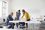 Businessman and two women in office having a meeting - RBF004035