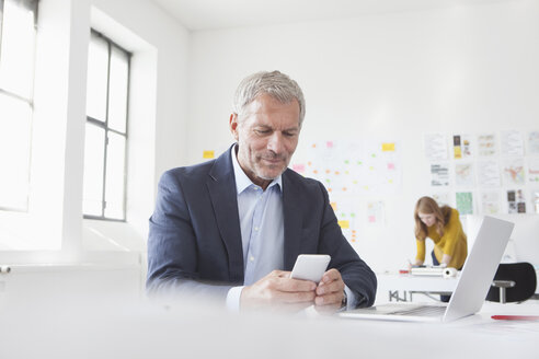 Businessman in office at desk looking at cell phone - RBF004044
