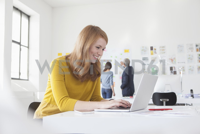 Smiling young woman in office at desk using laptop - RBF004047