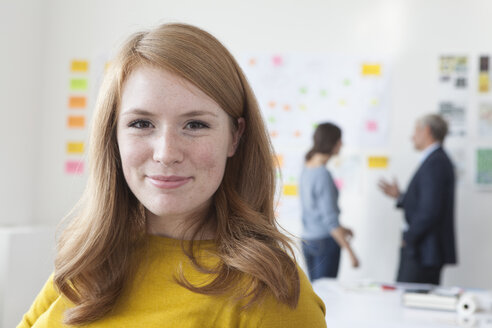 Portrait of smiling young woman in office - RBF004050
