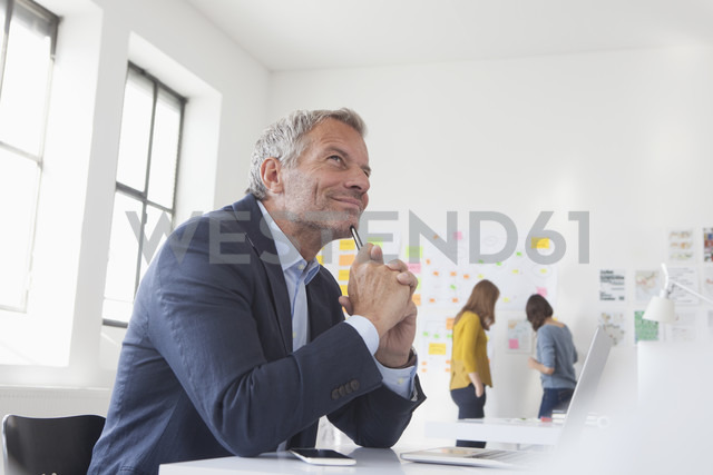Smiling businessman in office at desk thinking - RBF004053
