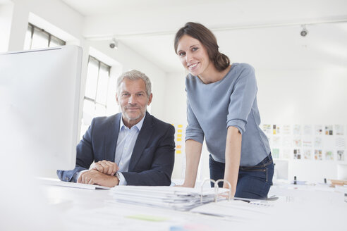 Portrait of smiling businessman and woman in office at desk - RBF004059