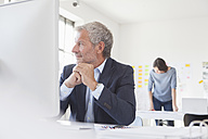 Smiling businessman in office at desk - RBF004062