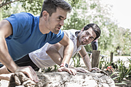 Two young men excercising together - ZEF007920
