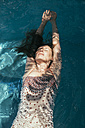 Woman floating on water of a swimming pool - MFF002608