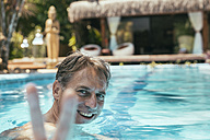 Brazil, Porto Seguro, portrait of happy man in a swimming pool showing victory sign - MFF002611