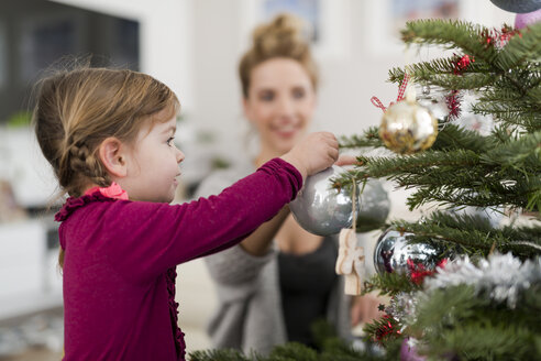 Little girl decorating Christmas tree with her mother in the living room - SHKF000434