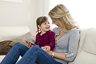 Mother and her little daughter sitting on couch in the living room with digital tablet - SHKF000437