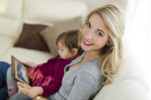 Portrait of smiling woman sitting with her little daughter on couch in the living room - SHKF000440