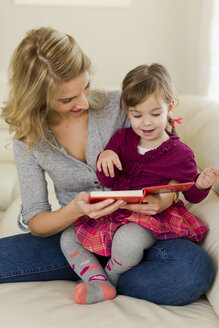 Little girl sitting on her mother's lap watching a book - SHKF000443