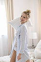 Portrait of laughing blond woman kneeling on bed holding pillow - SHKF000455