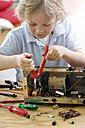 Little boy disassembling an old radio - GUFF000225